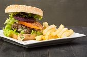 stock photo of hamburger  - Hamburger with fresh lettuce tomato and fries on wooden table - JPG