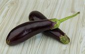 stock photo of brinjal  - Fresh bright raw Aubergines on the wooden background - JPG
