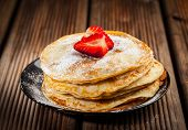 foto of sugar  - Pancakes or crepes with fresh strawberries and powdered sugar - JPG