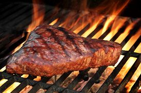 picture of braai  - Beef Strip Steak On The Flaming Hot Barbecue Grill - JPG