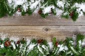 stock photo of snow border  - Christmas border top and bottom of frame with pine tree branches cones and snow on rustic wooden boards - JPG