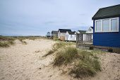 stock photo of beach hut  - Beach huts on sand dunes and beach landscape - JPG