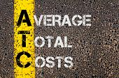 image of average looking  - Concept image of Business Acronym ATC as Average Total Costs written over road marking yellow paint line - JPG