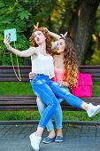 stock photo of pinup girl  - Best girlfriends make fun photos. Girl sits on her lap a friend. Group selfies. Girls dressed in the style of Pin-up girl. Hipster. The concept of true friendship.