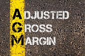 stock photo of grossed out  - Concept image of Business Acronym AGM as Adjusted Gross Margin written over road marking yellow paint line - JPG