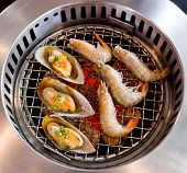 image of roster  - Closeup grilled seafood prawns and squids on fire background - JPG