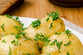 pic of boil  - Traditional Ukrainian food boiled new potatoes with butter and dill on wooden table - JPG
