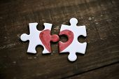 closeup of two separated pieces of a puzzle which together form a heart on a rustic wooden surface,  poster