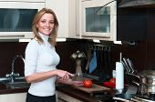 Beautiful Happy Smiling Woman In Kitchen Interior Cuts A Tomato