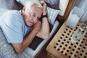 Senior man sleeping on bed at bedroom poster