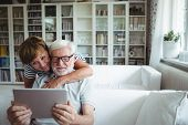 Senior couple using digital tablet in living room poster