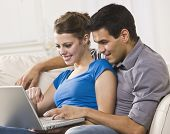 Attractive couple sitting together on a sofa and working on a laptop together. Horizontally framed p