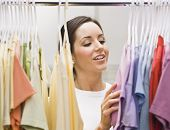 An attractive young female looking through a clothing closet.  She is smiling.  Horizontally framed