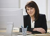 Attractive business woman stting at desk behind computer monitor smiling at camera. Horizontal.