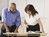 ein Geschäftsmann und Frau arbeiten zusammen in einem Büro. Sie sind auf der Suche von der Kamera entfernt.