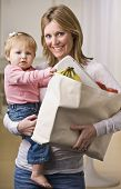 A young mother is holding her daughter in one arm and a bag of groceries in the other.  She is smili