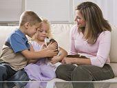 Een moeder en haar twee jonge kinderen spelen met een kleine puppy.  Ze glimlachen en kijken aw