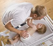 image of diaper change  - A young father is changing his baby daughter - JPG