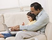 A smiling Indian father and daughter relax on the couch together and share a laptop.  Horizontally f