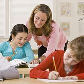 stock photo of students classroom  - Teacher helping student in classroom - JPG