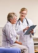 image of medical examination  - Doctor explaining medical chart to senior woman - JPG