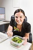 Businesswoman eating salad at desk