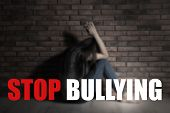 Message Stop Bullying And Sad Young Woman Sitting On Floor Near Brick Wall poster