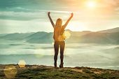 Happy woman tourist stay with open hands up on the green grass on the peak of mountain and look on t poster