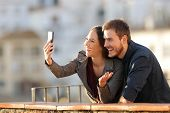 Happy Couple Having A Video Call Or Taking Selfies With A Smart Phone In A Balcony At Sunset poster