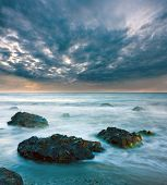 Sea landscape with stones in water before storm