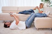 picture of dial pad  - Woman using her phone while her boyfriend is using a tablet computer in their living room - JPG
