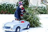 Healthy Little Smiling Kid Boy Driving Toy Car With Christmas Tree. Happy Child In Winter Fashion Cl poster