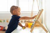 Little boy playing abacus for counting practice poster