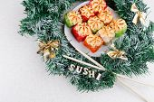 Christmas Sushi. New Year Sushi. Sushi And Christmas Wreath And The Word Sushi. View From Above. poster