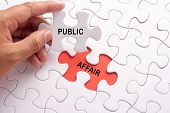 Hand Holding Piece Of Jigsaw Puzzle With Word Public Affair poster