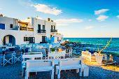 Sunshine view of white restaurant on turquoise stony bay of greek island Paros poster