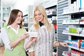 Female pharmacist advising customer at pharmacy