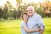 Attractive Smiling Mature couple portrait outdoors. Senior husband and wife in their 50s enjoying th poster