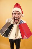 Happy Holidays Celebration. Man In Santa Hat With Bags On Orange Background. Christmas, New Year Sur poster