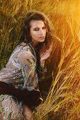 A portrait of a beautiful hippie girl is among a grass. Modern boho style. Beauty, fashion,  poster