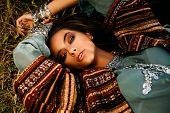 Beautiful hippie girl lying in a grass. Modern boho style. Beauty, fashion,  poster