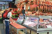 BARCELONA - JUNE 29: An unidentified tourist buys jamon in the La Boqueria market on June 29, 2011 i