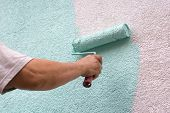 painting wall with a roll in green outdoor