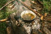 Herbal Tea In Cauldron Is Heats Up On Bonfire, Surrounded By Stones On Background Of Ashes Near Gree poster