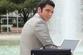Businessman using a laptop computer outdoors by a fountain