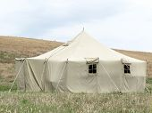 The image of millitary tent under the meadow