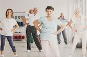 Smiling Elderly Woman Holding Hips During Gymnastic Classes For Senior People poster
