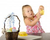 A cute little girl holding up the yellow flower she cut out of kiddie dough for Easter.
