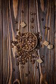 Top View Of Roasted Coffee Beans, Cane Sugar And Anise Stars On Wooden Background poster