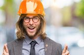 Young handsome architec man with long hair wearing safety helmet over isolated background smiling cr poster